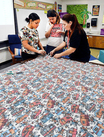 COMPASS students Deaira Jackson and Melissa Bernal-Garcia listens as para-educator Melanie Stohler shows them how to tie the cut ends of the blanket they are helping make Tuesday at as part of the school's third annual Day of Gratitude.