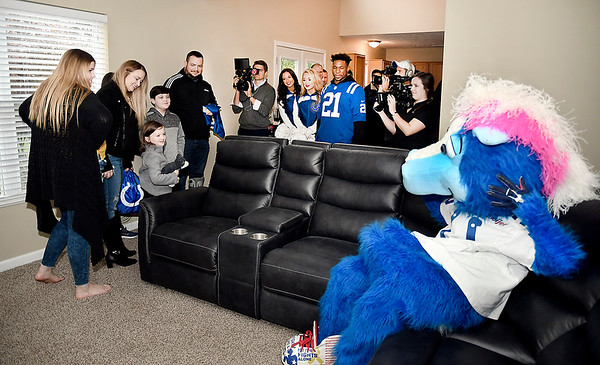 Indianapolis Colts mascot Blue tries out the new family room furniture first as Brian Sawyer and his family, left, check out the room after the Colts, Bob's Discount Furniture and Operation Homefront put all new furniture in their Anderson home.