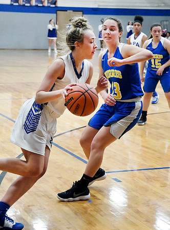 APA's Madison Stamm gets a step on Emily Adamowicz of Burris as she drives toward the basket.