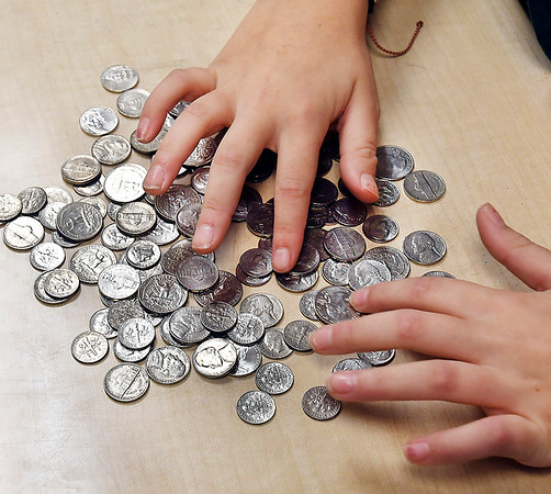 Students in Shannon Howell's Alexandria Intermediate School sixth grade class counting money that is being collected by the student body for the Make a Wish Foundation.
