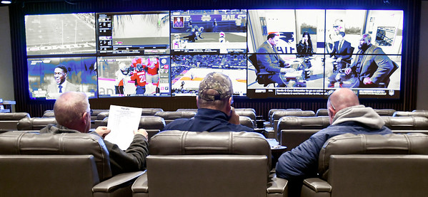 These patrons study the odd sheets for the different sports they want to bet on while sitting in front of the large TV screens in The Book, Hoosier Park Racing & Casino's sports betting facility.