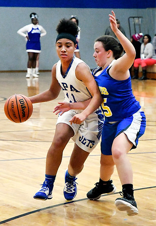APA's Tommya Davis drives toward the basket as Burris defender Jenna Lis tries to block her path.
