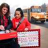 Mandy Webb, left, assists ACS teacher Renee Bynum find her bus assignment Tuesday morning as more then 300 teachers from Anderson Community Schools were heading to the Statehouse for the Red for Ed rally.