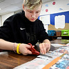 Seventh grade COMPASS student Max Krieg uses a pattern as she cuts strips along the edge of the blanket material.