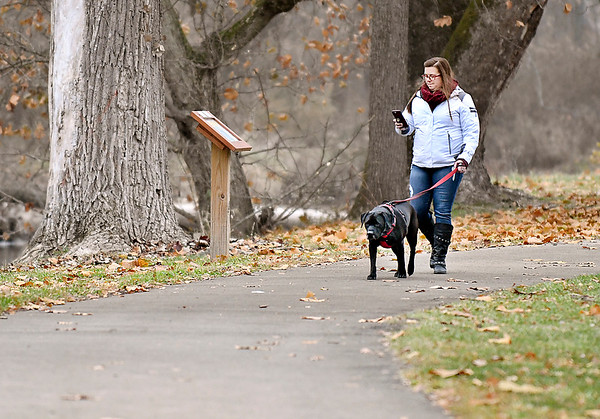 Samantha Hyde, of Pendleton, checks her phone as she walks Gage, her five-year-old pit/lab mix dog, along Fall Creek in Falls Park in Pendleton this week.