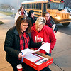 Mandy Webb, left, assists ACS teachers get their bus assignments Tuesday morning as more then 300 teachers from Anderson Community Schools were heading to the Statehouse for the Red for Ed rally.