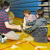 """From left, Jacob, Julia and Conner Martin piece together a dinosaur puzzle as the Children's Museum of Indianapolis presented """"Puzzling Dinosaurs"""" during Literacy Night at Eastside Elementary School on Wednesday."""