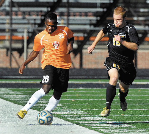 AU's Guimps Pierre beats Manchester's Andrew Gray to the ball during their soccer match Wednesday.