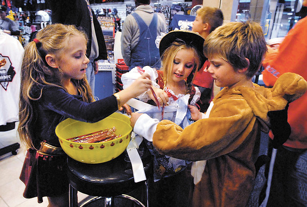 """""""Super Girl"""" Page Parker, 6, and """"Pirate Princess"""" Hadlee Eppards, 5, pass out candy at Squeeze Play to trick-or-treaters Monday evening during the Mounds Mall Malloween extravaganza.  Here they double-up on candy to halloweener Logan Berry, 6."""