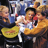 """Super Girl"" Page Parker, 6, and ""Pirate Princess"" Hadlee Eppards, 5, pass out candy at Squeeze Play to trick-or-treaters Monday evening during the Mounds Mall Malloween extravaganza.  Here they double-up on candy to halloweener Logan Berry, 6."