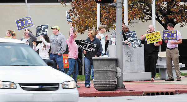 Protesters against cuts to emergency services gathered outside the Anderson City Building Tuesday afternoon before the Anderson City Council special meeting to show their support for the police and fire departments.