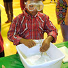 """Nyrel Ingram, 6, excavates a fossil as the Children's Museum of Indianapolis presented """"Puzzling Dinosaurs"""" during Literacy Night at Eastside Elementary School on Wednesday."""