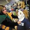 Ashley Stephens, of Pendleton, helps her son Ian, 8, try on masks as they shop for Halloween at the Spirit Halloween store in Anderson Friday.