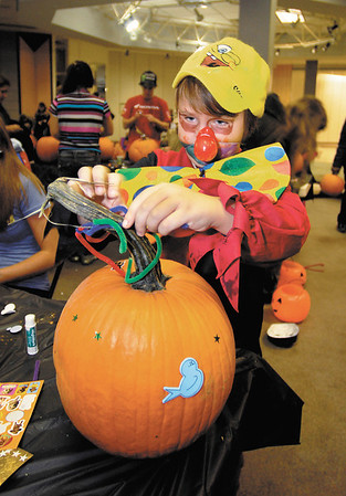 Daniel Painter, 8, of Middletown, works on decorating his pumpkin he got at the Mounds Mall Malloween extravaganza Monday evening.