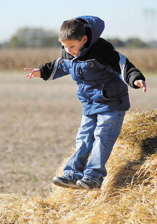 Andrew Teaney jumps off a bale of hay as Pendleton Elementary students visit Smith Family Farms during a field trip on Thursday.