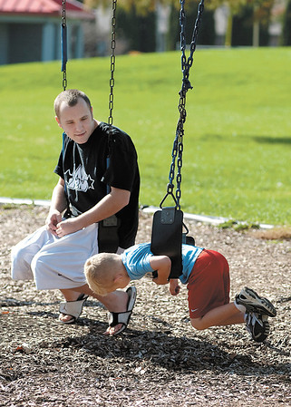 Tyler Rinker enjoys the warm weather with his son Owen Rinker, 5, at the playground in Pulaski Park Thursday afternoon.  Owen twirls himself around in his swing as dad rests from pushing him earlier.  ACS being on fall break gave the kindergartener the day to spend with his father.