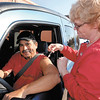 Bev Hilburt, a registered nurse at Saint John's Medical Center, gives Bobby Garcia a flu shot as he sits in his vehicle during the hospital's drive-through flu shot offering Wednesday.