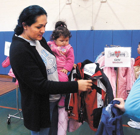 FILE PHOTO: Libey Billar carries her one year old daughter Biancy as she looks at coats for her children at the Coats of Caring distribution Saturday morning.
