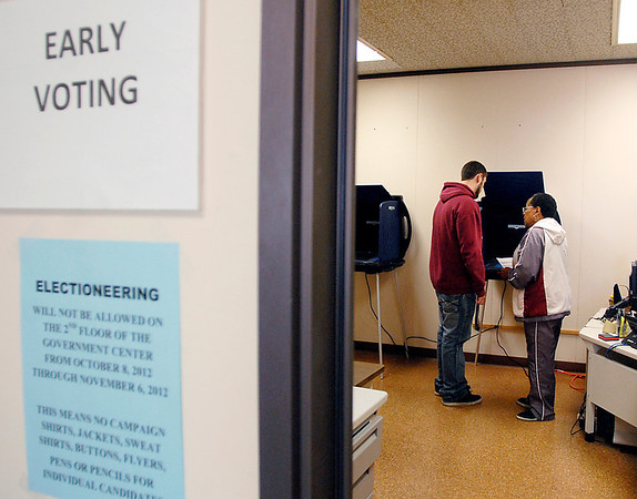 Early voting for the November 6th general election started Monday at the Madison County Government Center.  Here election room worker Bev Lewis shows Michael Whitsell-Sherman how to use the electronic voting machine since he is a first-time voter.  Michael decided since he was a new voter he would go exercise his right on the first day available.
