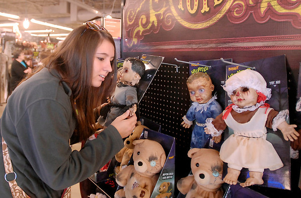 Marcie Pratt of Anderson listens to the sounds of one of the Evil Toys as she shops at Spirit Halloween Saturday.