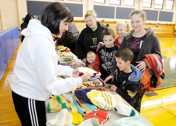Don Knight/The Herald Bulletin<br /> Community Hospital Anderson CEO Beth Tharp helps from left, Danielle Rust, Chase Rust, Jeremiah Bays, Brooklynn Hayslip, Heather Wisler and Keegan Bays pick out hats during Community's Coats for Caring distribution on Saturday.