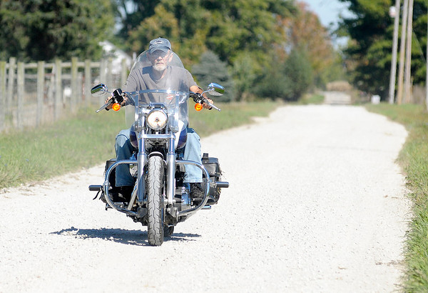 Don Knight/The Herald Bulletin<br /> Bruce Hanson rides his Harley Davidson motorcycle on Henry County Road 950 West on Friday. Hanson lives on the road that was formerly paved but was converted to gravel by the county in order to save money on maintenance.