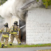 Don Knight/The Herald Bulletin<br /> From left, AFD's Dan Siek and Wilbur Kelly extinguishes a garage fire on the alley south of West 13th on Wednesday.