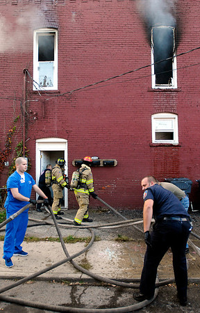 Fire personnel help feed hose into the stairway at 231 East 13th Street to get to a second floor apartment fire that broke out about 6 p.m. Monday.