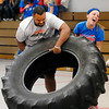 Elwood High School senior Anthony Bennett and sophomore Taylor Noone struggle with flipping the large tire during one of the activities of the Red Ribbon Rally Battle of the Schools held at the Impact Center Saturday.