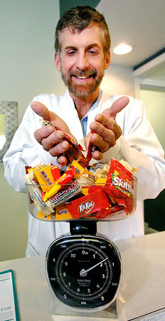 Dentist Dr. Gregg Horstmeyer weighs Halloween candy in his office that he  purchases from people coming to his office for $1 a pound, up to five pounds per family, and then he sends the candy to Operation Gratitude, a national program where care packages are sent to the military.