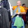 Star Bank employee Jonathon Jacoby uses his chin as he sorts donated clothing items at Dove Harbor Monday as part of Star Bank's community service day.