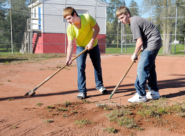 """Don Knight/The Herald Bulletin<br /> From left, Justin McIver and Devon Raper weed the baseball diamond at Shadyside Park as Liberty Christian students fanned out to 15 locations to complete service projects as part of the school's """"Servathon"""" on Friday."""