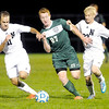 Don Knight/The Herald Bulletin<br /> Pendleton Heights' Evan Dix dribbles the ball as he is chased by Noblesville's Andrew Boyum (11) and Evan Blissitt (23) during the sectional semi-final at the White River Soccer Fields in Noblesville on Wednesday.