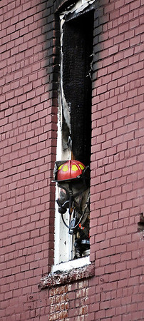 A Anderson firefighter sticks his out of the window of a second floor apartment at 231 East 13th Street where a fire broke out about 6 p.m. Monday.