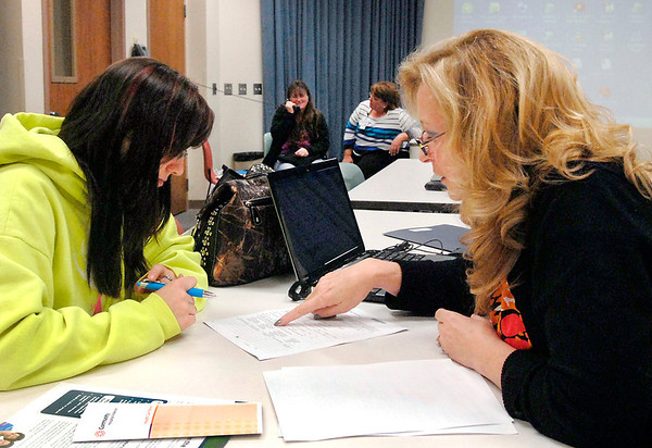 Emily Thornburgh, left, of rural Henry County, fills out papers with assistance from Priscilla Engle, right, Community Hospital social worker, at the hospital's enrollment session for Indiana's Health Insurance Marketplace Tuesday morning.