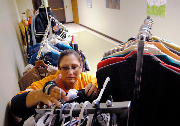 Star Bank employee Vivian Lawless sorts out donated clothing items and hangs them on racks at Dove Harbor Monday as part of Star Bank's community service day.  Lawless, and 14 other employees, cleaned gutters, trimmed shrubs, painted, moved furniture, and sorted donations for Dove Harbor.<br /> <br /> <br /> <br /> Employees of Star Bank spend their Columbus Day off doing community service for area agencies.