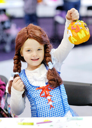 """Don Knight/The Herald Bulletin<br /> Dressed as Dorothy from """"The Wizard of Oz,"""" Kenna Kane, 6, holds up her pumpkin after decorating it during the Malloween Extravaganza at Mounds Mall on Tuesday."""