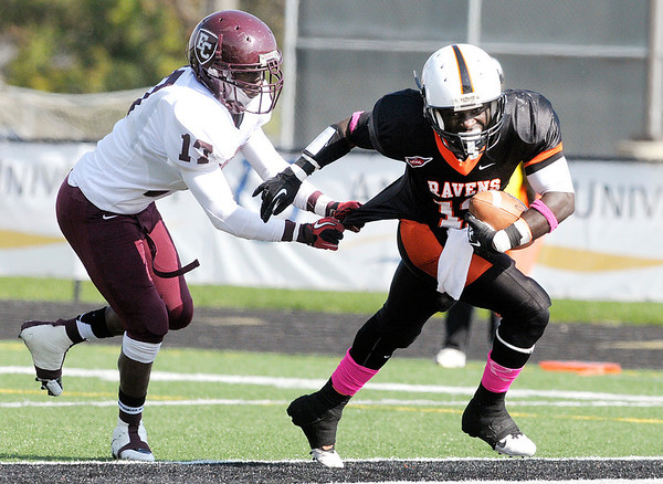 Don Knight/The Herald Bulletin<br /> Anderson's  Edward Pupoh scores a touchdown as he is pursued by Earlham's Denis Caulley during homecoming on Saturday.
