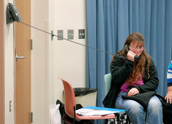 Kathy Abner, of Muncie, waits on the phone to talk to someone for assistance as she came to Community Hospital's enrollment session Tuesday morning for Indiana's health Insurance Marketplace signup.  Counselors tried to go online to sign Abner up but couldn't log in, then tried calling and after more then 30 minutes on hold to talk to a person to assist her she was told they could answer her questions but she needed to enroll through their web site. After more then 2 hours Abner left without signing up for any plan.