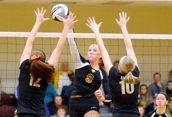 Don Knight/The Herald Bulletin<br /> Alexandria's Allie Hueston attacks as Madison-Grant's Jessica Hull (12) and  Chloe Stitt (10) try to block her during the the sectional final on Saturday.