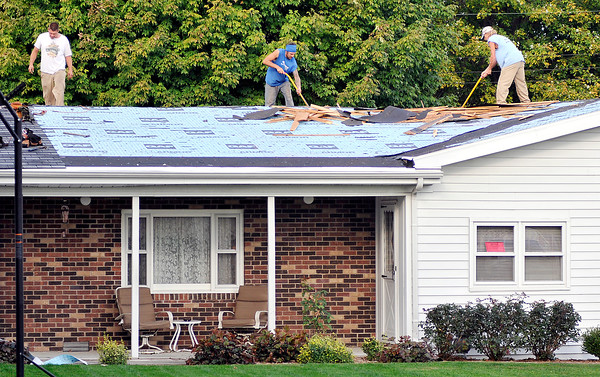 John P. Cleary | The Herald Bulletin<br /> Workers from Unique Home Solutions work on roof at 4505 Pitt Street this past Wednesday where Betty Palmer has had issue with the company.