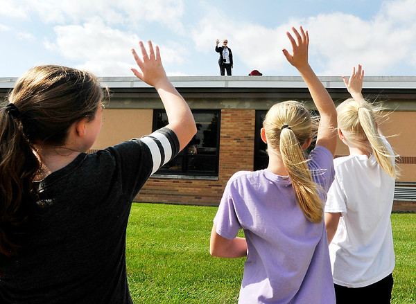 John P. Cleary    The Herald Bulletin<br /> Lapel Elementary School principal Genny Zetterberg waves to students as she spends the school day Monday on top of the school roof after students surpassed the goal for the school's annual Dog Jog fundraising event. The students raised almost $26,000 surpassing their goal of $24,000.