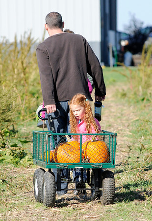 Don Knight | The Herald Bulletin<br /> Phoebe Smith, 5, gets a lift out of the pumpkin patch riding in a wagon pulled by Shannon Smith as the family from Westfield visited Smith Family Farms in Pendleton. The pumpkin patch is open today and next weekend from 11 a.m. to 5 p.m.
