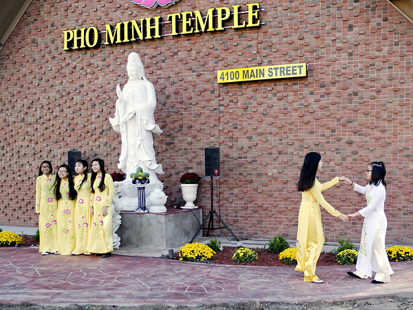 Mark Maynard | For The Herald Bulletin<br /> Two attendants dance together while others pose for a photograph prior to the dedication of the Pho Minh Buddhist Temple on Sunday.