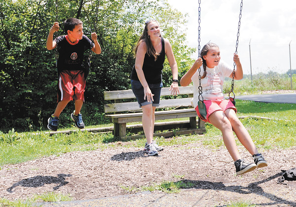 Don Knight | The Herald Bulletin<br /> Shirley Payne plays with her children Aliya and Alex in the campground playground during a walk at Mounds State Park in July.