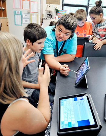 John P. Cleary |  The Herald Bulletin<br /> Elwood Elementary School second grader Kileigh Hughes, left, asks a question as teacher Carrie Bowman, right, explains to her and classmate Cayden Timmons, middle, the concept of the class project they are about to start.