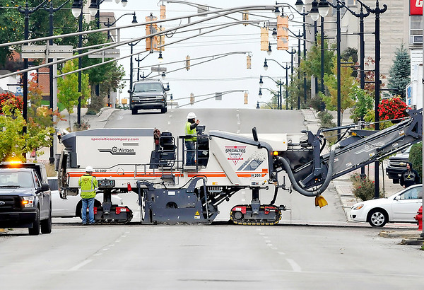 John P. Cleary |  The Herald Bulletin<br /> Drivers moving through downtown Anderson Thursday had to work around large equipment as E & B Paving worked through downtown grinding down the old pavement along Eighth Street in preparation for paving Eighth Street through town. This view is looking south along Jackson Street as the grinder crosses the intersection.