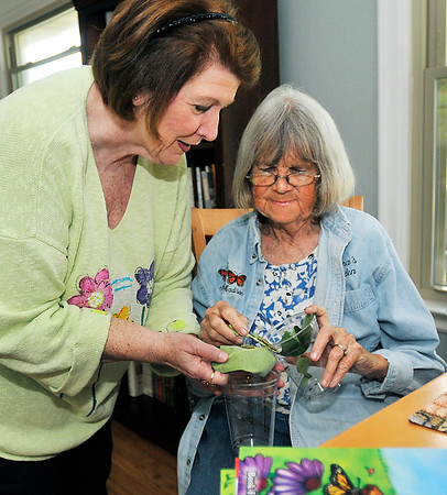 "John P. Cleary |  The Herald Bulletin<br /> Nancy Zimmerman holds out her hand as Loretta Heiniger gets out one of the catterpillers she's broght Nancy along with a couple of monarch butterflies. Heiniger, known as the ""butterfly lady"" is who inspired Zimmerman to write her latest book."