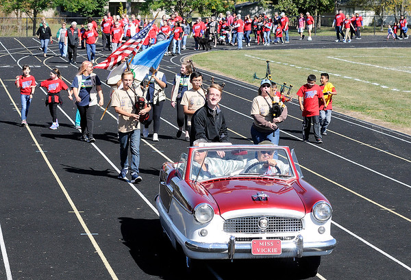 Don Knight | The Herald Bulletin<br /> Barry and Kathy O'Connor lead the Friends of the Poor Walk in Miss Vickie, a 1957 Nash Metropolitan, as Father Daniel Shine rides in the back at Highland Middle School on Saturday. The event is a benefit for St.Vincent de Paul, the Catholic lay organization that provides assistance to lower income families to help with rent, utilities, food, and other items.