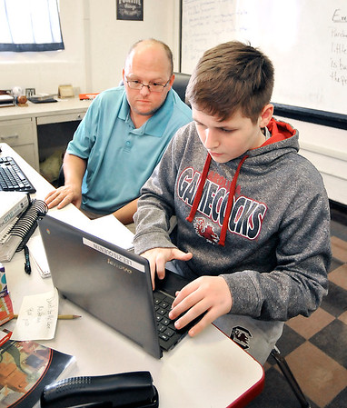 John P. Cleary    The Herald Bulletin<br /> Liberty Christian teacher Chad Lee works with freshman student Quentin Edmonds-Long in his Sports and Entertainment Marketing class.